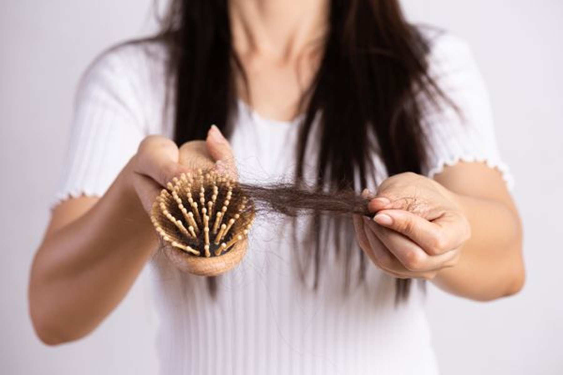 Mulher com escova nas mãos demostrando queda de cabelo