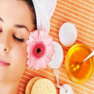 Mulher deitada ao lado de um pote de máscara de mel